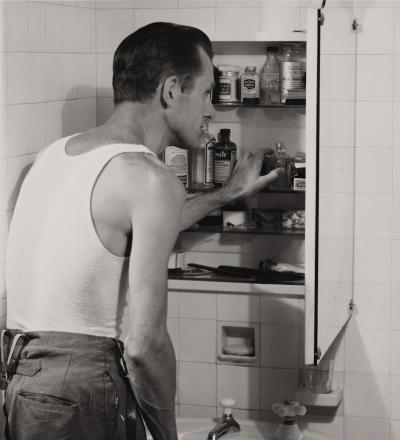 A man looks through his medicine cabinet in the bathroom, circa 1955
