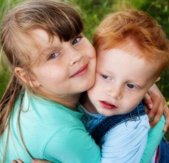 Happy little girl hugging her brother