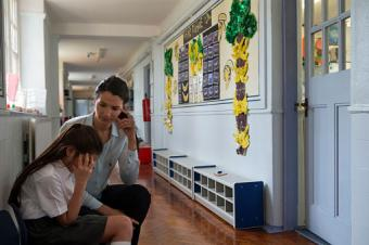 Supportive teacher talking with bullied girl