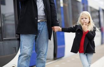 girl traveling on public transport with her father