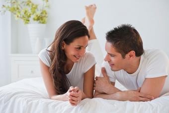 Hispanic couple laying on bed talking