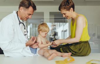 Pediatrician vaccinating toddler