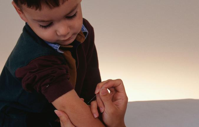 Boy receiving acupuncture to arm