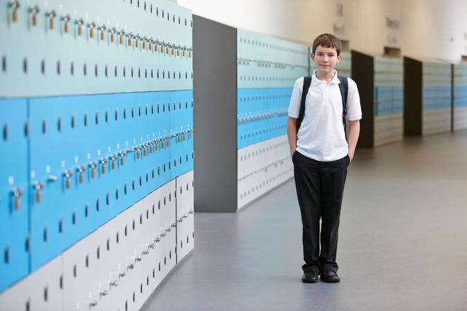 Boy standing in school hallway