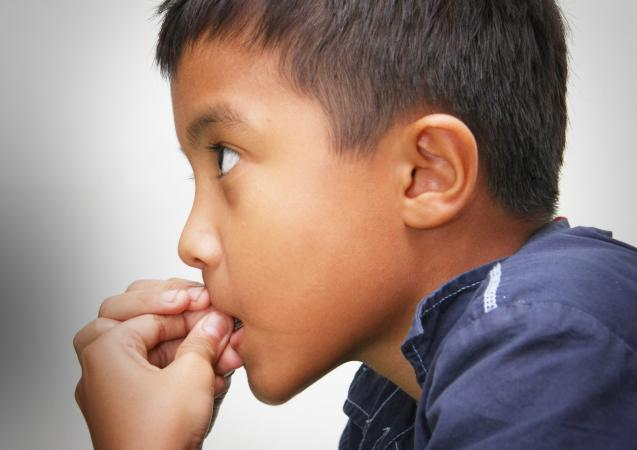 Young boy chewing on fingers