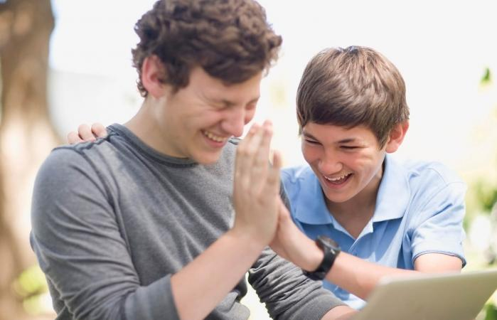 Teenage boys using laptop together