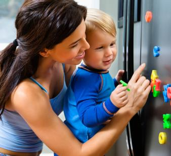 Toddler and mother with magnets on refrigerator