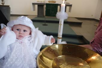 Baby beside font about to be baptized