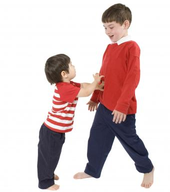 toddler pushing older brother isolated background