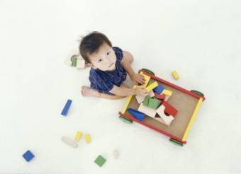 boy putting blocks in wagon