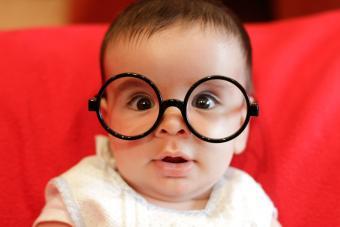 Closeup of baby wearing black glasses