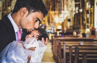 Man Kissing Baby Girl On Forehead In Church