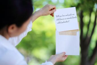 Woman's Hand Pulling White Card From Envelope