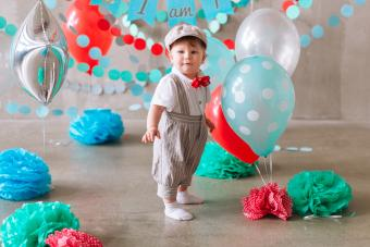 Cute baby boy first birthday party decorated with garland and balloons