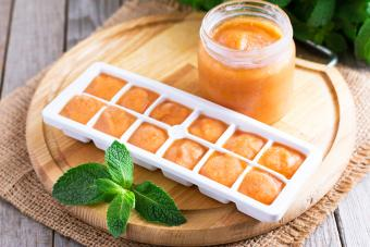 Ice tray with fresh vegetable puree on wooden background