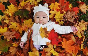 Baby Girl Lying On Autumn Leaves