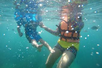 Woman And Boy Swimming Undersea
