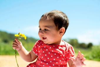 Smiling Girl Holding Yellow Flowers Against Sky