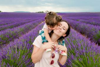 Mother and daughter walking among lavender fields in the summer