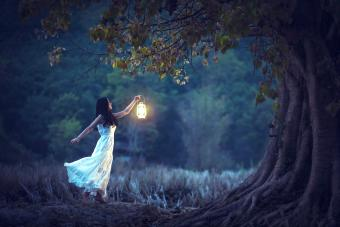 Beautiful girl in white holding a lantern in the autumn forest shining under the trees