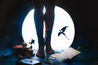 Girl with dragon and knight silhouettes against shiny moon background