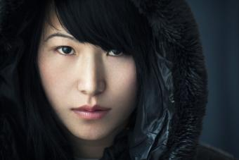 Asian girl with blank expression wearing black hoody jacket