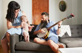 Father playing music to baby and wife at home