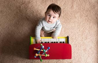 cute baby boy playing toy piano
