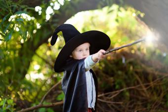 Little boy in pointed hat and black cloak playing with magic wand outdoors