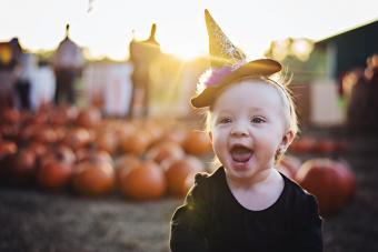 Baby girl crawls through pumpkin patch
