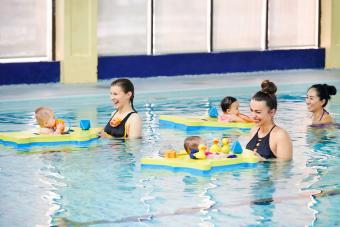 Shot of mothers enjoying themselves with their babies at swimming class