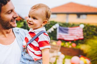 Father and son celebrating Fourth of July in their yard