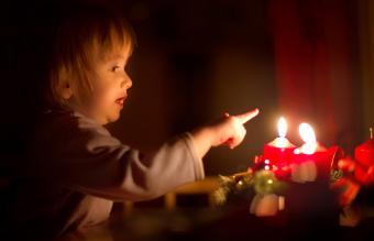Boy about to touch burning candle