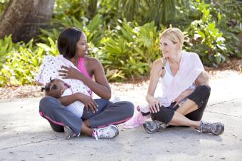 Mothers chatting while nursing babies outdoors