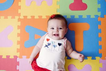 Cute baby girl relaxing on colorful alphabetical puzzle playmat
