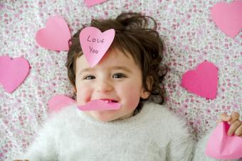 Baby girl with pink heart-shaped post it stickers