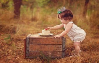 girl wearing a crown reaching for cake