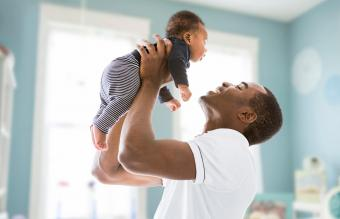 father lifting baby son