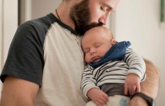 father kisses sleepy newborn