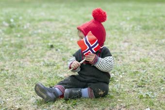 Child sitting on grass holding Norwegian flag