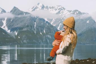 Mother with baby traveling and enjoying mountains view