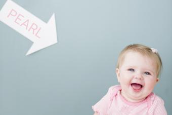 Baby girl near arrow with name Pearl