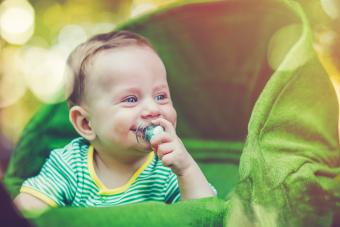 Cute baby in carriage outdoors in summer
