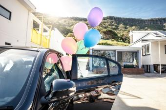Woman holding baby colored balloons out of a car