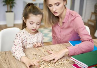 Focused child learning the alphabet with her nanny