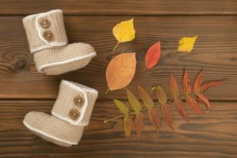 Hand made crochet baby booties and Autumn fallen multi-colored leaves