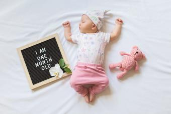 Sleeping one month old newborn baby girl laying between letter board and teddy bear