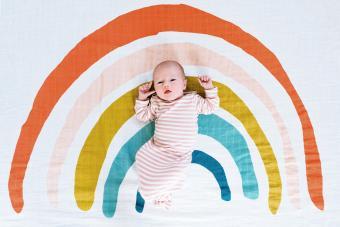 Newborn baby on a rainbow colored blanket