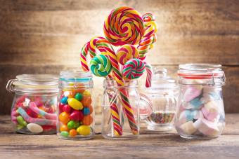 Colorful candies, jellies, lollipops, marshmallows and marmalade in a glass jars