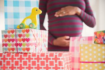 pregnant woman admiring gifts at baby shower